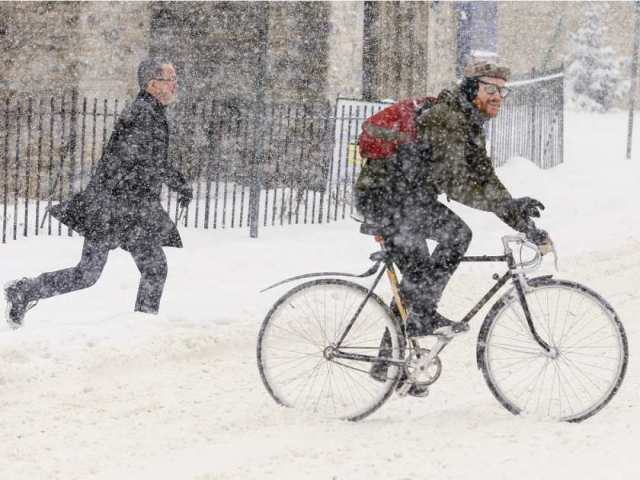 a-cyclist-and-pedestrian-cross-elgin-street-in-ottawa-during